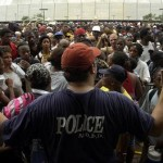 A New Orleans Police Department employee tries to calm a massive crowd of Hurricane Katrina refugees waiting outside the Louisiana Superdome in New Orleans Thursday, Sept. 1, 2005.